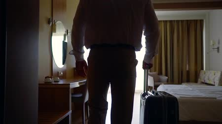 Войти : adult strong man is entering in hotel room, he is rolling his suitcase near, back view of his body