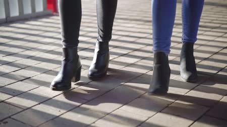 sokak : Close-up shot of legs of two women keeping pace in city, walking in black boots. Stok Video