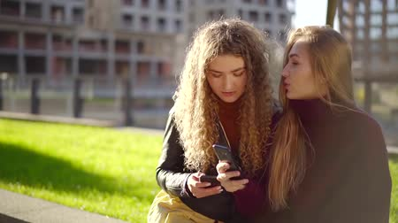 scholar : two female friends are sharing contacts from their mobile phones, sitting in lawn in sunny day