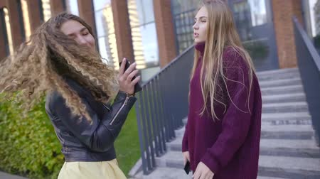 scholar : attractive young women are dancing and singing songs outside near buildings in city