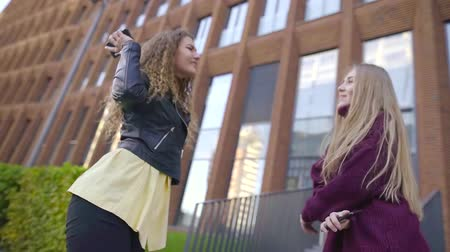 chlapík : funny students girls are dancing in front a building of university in autumn day, switch on music