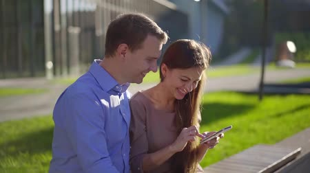 fiancee : young woman with her boyfriend are sitting on a bench outside and watching pictures in smartphone Stock Footage