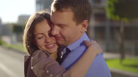 nişanlısı : happy loving heterosexual couple is hugging on city street, turning heads to camera, close-up Stok Video