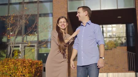 nişanlısı : cheerful young woman is walking with her boyfriend in city in sunny fall day, they are holding hands Stok Video