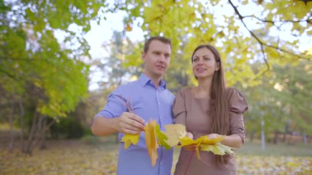 異性のカップル : cheerful loving couple is throwing maple leaves in air in daytime in autumn forest, laughing 動画素材