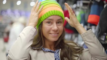 şey : smiling female shopper is demonstrating bright knitted hat on her head in a hall of clothing store