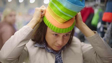 головной убор : charming middle aged woman is trying vivid striped knitted hat and looking to camera, smiling