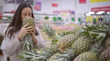 tayın : adult female shopper is sniffing and touching pineapples in a store, choosing fruits for family Stok Video