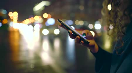 many lights : close up. female hand with manicure holding a cell phone on the background of night city and highway with lots of traffic