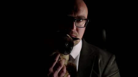 siamese : man in a suit sits in the dark with his pet cat Siamese breed