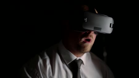 another : business man with pleasure playing virtual reality after work in the dark. dive into another computer world