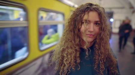 fare : portrait of a young woman with curly long hair in the subway. on the background of a passing train cars