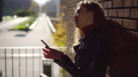 kıvırcık saçlar : Side view shot of a charming young girl in leather jacket using smartphone and leaning on a brick wall outdoor.