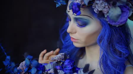 výstřední : amazing halloween makeup and hairstyle in blue colors on young woman, girl is looking on flowers Dostupné videozáznamy