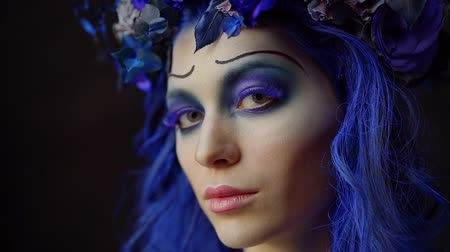 face painting : young charming model with creative makeup in blue colors on her face and blue hair, smiling and posing