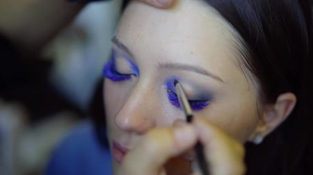 výstřední : makeup artist is drawing by blue shadows on upper eyelids of young female model, performing make-up