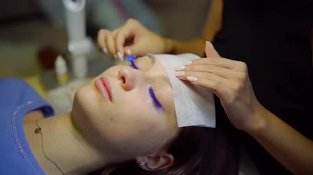 výstřední : cosmetologist is brushing blue fake eyelashes of young female model lying with closed eyes Dostupné videozáznamy