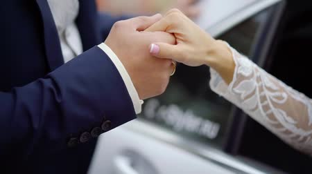 растягивается : groom is kissing hand of his beloved bride, stretched from car windows in ceremony day, closeup of hands