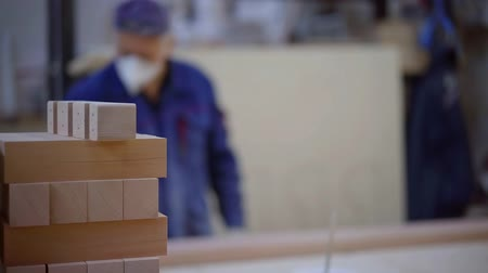 desfocado : wooden details are folded in workshop in foreground, worker with protective mask