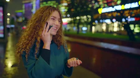 veselí : cheerful girl is talking by mobile phone standing alone on street in night time, speaking loudly