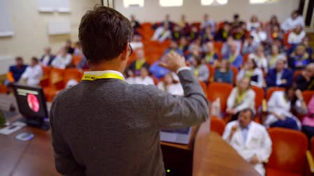 speach : Shot from behind of a male doctor giving an educational speech on a conference, new information for medical staff.