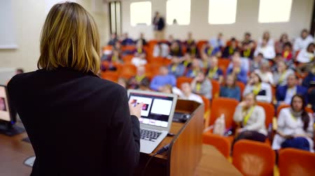podium : Shot from behind of a businesswoman giving a lecture on a business event, big audience.