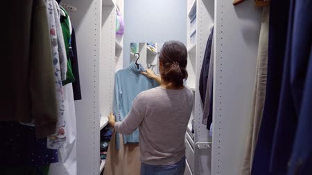 решить : Woman choosing clothes in her home wardrobe for going outside.