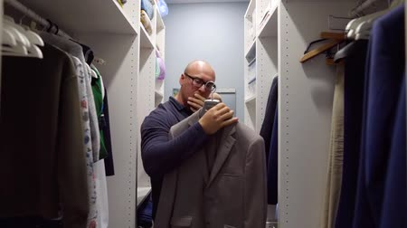 casual wear businessman : Serious man choosing suit jacket in big home closet.