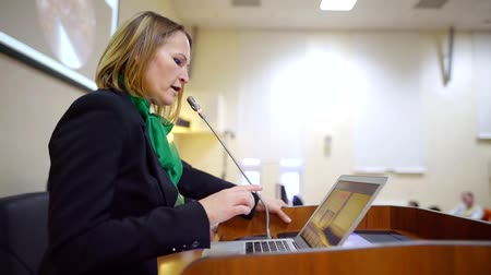 подиум : Middle-aged female businesswoman giving a presentation in a conference room, reading from the laptop. Стоковые видеозаписи