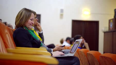 political speech : adult woman is sitting in auditorium in lecture, working on notebook, preparing for presentation