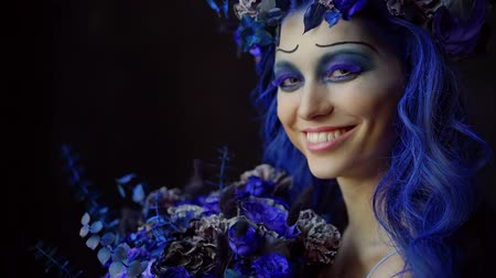 výstřední : creative blue makeup, hairstyle and floral decoration on charming smiling young woman, artistic image Dostupné videozáznamy