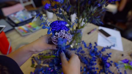 yapıcı : florist is making creative blue bouquet, rotating flowers in hands, painting by blue color, close-up