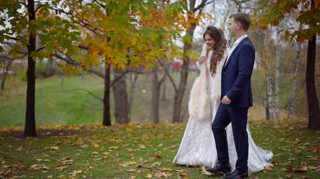 nowożeńcy : happy bride with her groom is walking in autumn park in their wedding day, strolling along lake