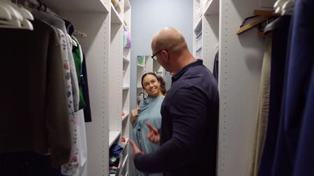 sobre : adult woman is consulting with her husband about garment, they are standing in dressing room
