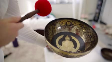 tibeti : specialist is striking on copper tibetian bowl during nada massage, holding it over patient body Stock mozgókép