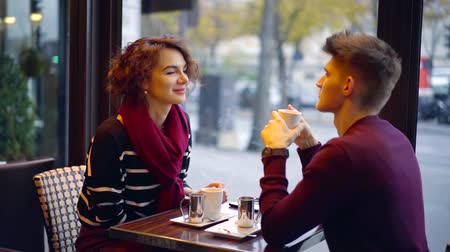 eleven : cute brunette girl is chatting joyfully with handsome young man in cafe, drinking coffee in daytime Stock mozgókép