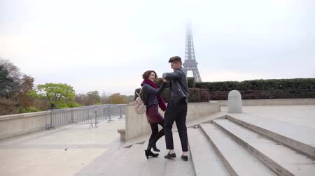 pařížský : man and woman are dancing and moving down over stair outdoors in city, Eiffel tower is in background