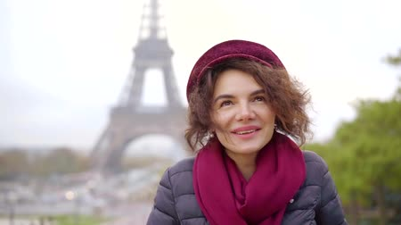 parisli : happy townswoman is smiling and looking at camera in Paris in autumn day, Eiffel tower