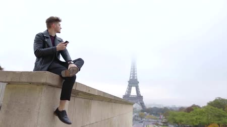 tur : alone handsome man is sitting on stone wall in Paris in fall day, reading messages in mobile phone