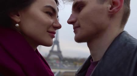 eiffel : loving pair is approaching to each other against Eiffel tower looking to faces with love and passion