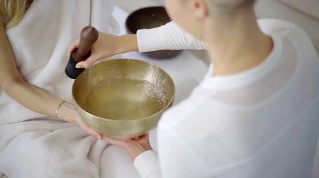 mantra : physician woman is touching and rotating stick-resonator around metal bowl in nada therapy