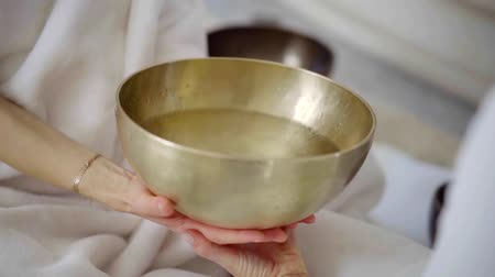 move well : two women are holding large copper bowl with water by hands, therapist is striking on it Stock Footage