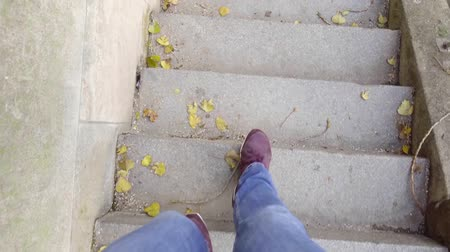 stepping : man is lowering by stone stair on a street in autumn day, top view on legs, filming himself