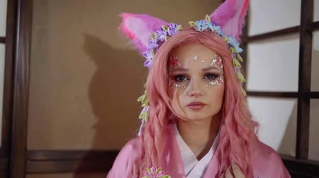 косплей : funny girl with fake cat ears on head and pink hair, sitting alone in room, posing and flirting
