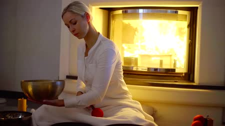 recuperação : Beautiful female therapist plays singing bowl indoor by the fireplace, sound massage.