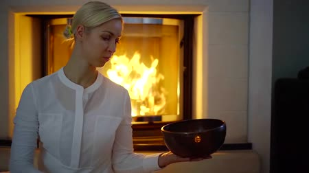 tybet : Blonde woman in white shirt sitting alone in a room and playing singing bowl, fireplace on a background. Wideo