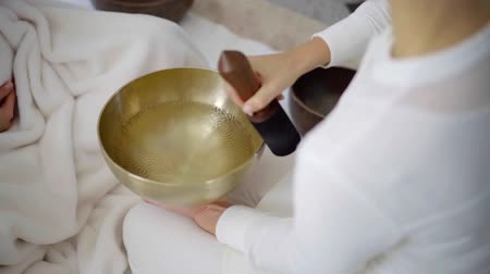 alternativní medicína : Female spa therapist performing tibetan singing bowl massage.