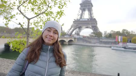 pařížský : Portrait of a beautiful woman by the river wearing warm clothes outdoor in autumn in Paris.
