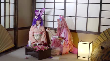 манга : Two women dressed as anime characters performing traditional japanese ceremony.