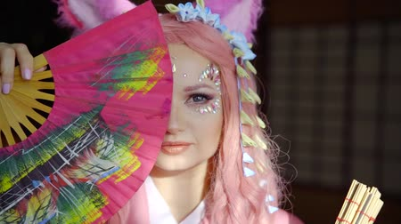 washitsu : Beautiful girl in pink kimono with pink wig and bunny ear on her head posing with colorful fan in japanese scene. Stock Footage